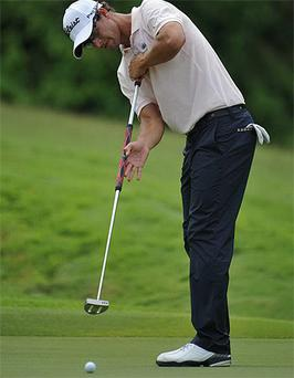 Adam Scott of Australia putts with his broom handel putter