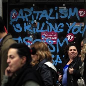 Protesters march past a closed shop whose window is covered in graffiti during a union protest in Thessaloniki, Greece (AP)