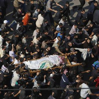 Palestinian mourners in Gaza carry the body of Hamas' top military commander Ahmed Jabari, killed in an Israeli strike (AP)