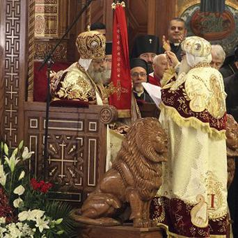 Pope Tawadros II, 60, sits on the throne of St Mark in the Coptic Cathedral in Cairo, Egypt (AP)