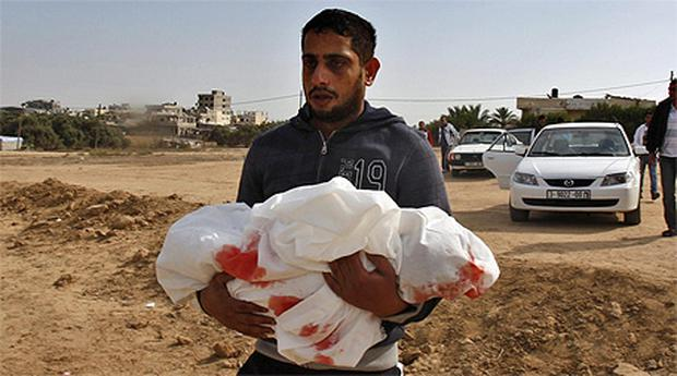 Palestinian Yoused Abu Khoussa carries the body of his one-year-old son Iyad who was killed in Israeli strikes on Sunday