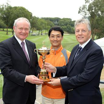 Peter Robinson and Martin McGuinness holding the Ryder Cup with Chi-Won Yoon, Chief Executive Officer of UBS Asia Pacific