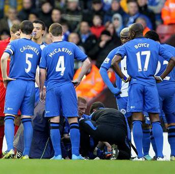 Ben Watson, sitting, fractured a shin in Wigan's match with Liverpool on Saturday