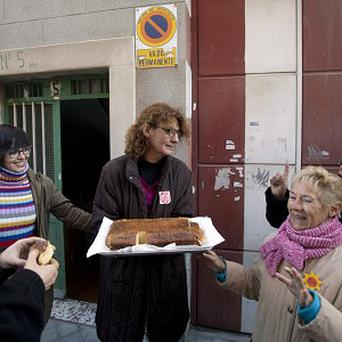 A Spanish home owner feeds the media as she waits to be evicted (AP)