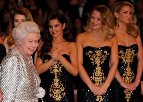 Britain's Queen Elizabeth walks past Girls Aloud as she arrives to greet the performers after the Royal Variety Performance at the Royal Albert Hall in London November 19, 2012. REUTERS/Andrew Winning (BRITAIN - Tags: ROYALS ENTERTAINMENT)