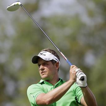 Luke Donald watches his tee shot on the second hole in Dubai