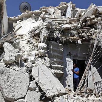 A Syrian man looks out of the rubble after an earlier Syrian government airstrike in Aleppo (AP)