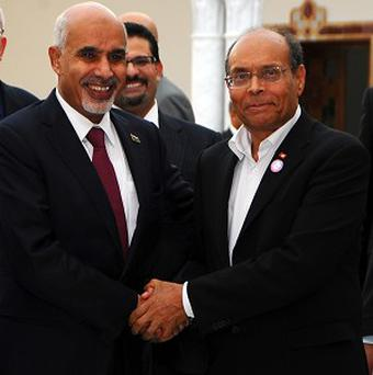 Tunisia's President Moncef Marzouki, right, greets Mohammed al-Megarif, President of the General National Congress of Libya (AP)