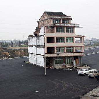 The duck farmer's house stands stranded in the the middle of a new main road near Wenling city in east China (AP)