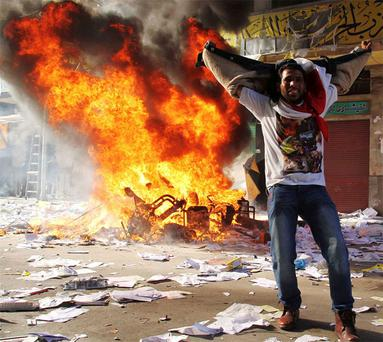 A protester cheers as items ransacked from an office of the Muslim Brotherhood's Freedom and Justice Party burn. Photo: Reuters