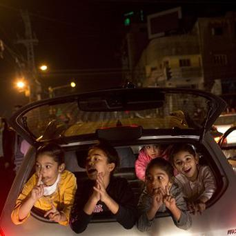Palestinians celebrate the ceasefire in Gaza City (AP/Bernat Armangue)
