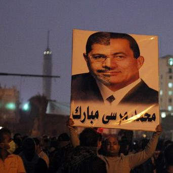 A protester holds up a poster with the faces of former Egyptian President Hosni Mubarak and current President, Mohammed Morsi as public anger mounts that Mr Morsi is seizing too much power (AP)