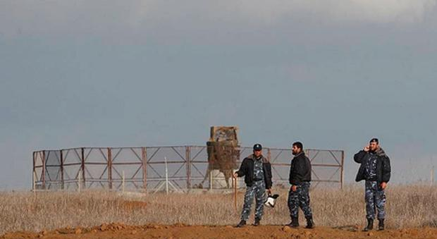 Members of Hamas security forces stand guard in front of an Israeli watchtower as they prevent people from reaching the fence between Israel and the southern Gaza Strip.