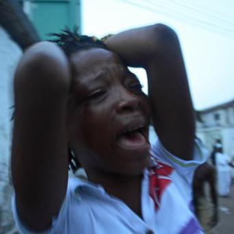 A supporter of the opposition Sierra Leone People's Party cries outside a party office after the election result (AP/Tommy Trenchard)