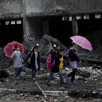 Palestinian schoolchildren walk in debris by a damaged school in Gaza City (AP)