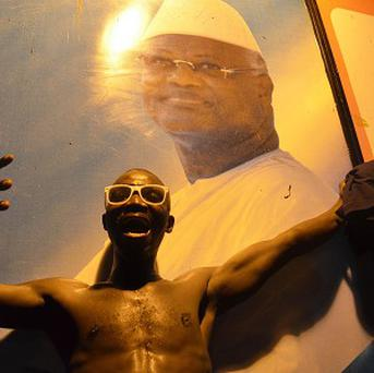 A supporter of the ruling All People's Congress celebrates next to a poster of incumbent President Ernest Bai Koroma (AP/Tommy Trenchard)