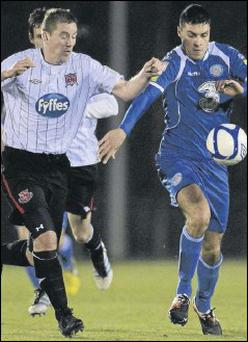 Liam Burns closes down Waterford's Daragh Walsh shortly before limping off with an injury.