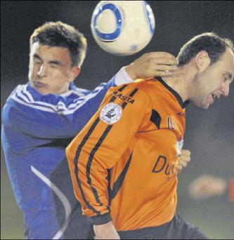 Barry Walsh (Quay Celtic) goes head to head with Karl Martin of Dromin United at Clancy Park on Friday night.