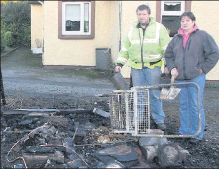 Anna Mai White and neighbour David Glennon by the remains of her burned-out shet at Moutnain View in Rathnure.