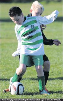 A Skerries Town player holds off a challenge from his Swords Celtic opponent during their U-11 clash.