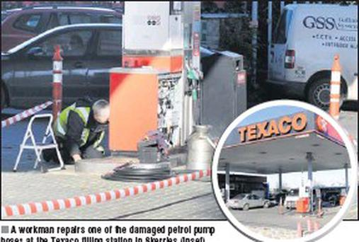 A workman repairs one of the damaged petrol pump hoses at the Texaco filling station in Skerries (inset).