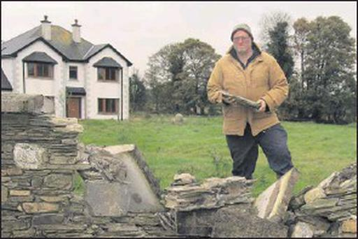 Michael Doyle by the wall outside his house after the most recent accident there.