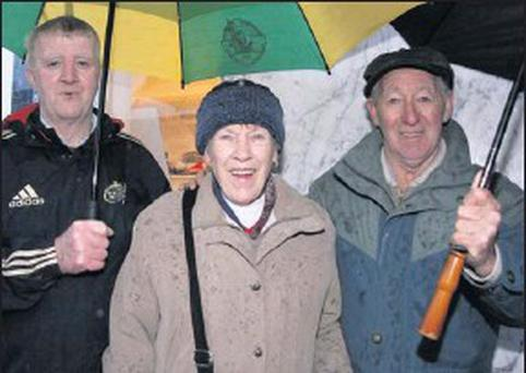 John Joe O'Connor, Brosna (left) pictured with his neighbours, Bridget and Michael Lenihan taking shelter from a downpour at the annual Castleisland November 1 Horse Fair on Thursday. Credit: Photo by John Reidy