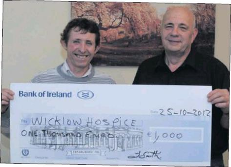 RIGHT: Thomas smith presenting the cheque for €1,000 to Bill Porter of the Hospice Committee.