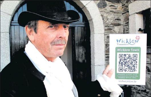 Shay Brennan, Gaoler at Wicklow's Historical Gaol showing the dedicated QR Code (SEE BELOW) poster to Wicklow Town's page on visitwicklow.ie
