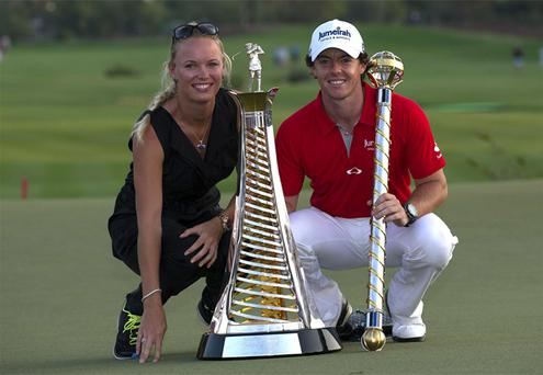 Rory McIlroy holds the trophy with his girlfriend and Tennis player Caroline Wozniacki of Denmark after he wins the final round of DP World Golf Championship in Dubai. Photo: AP