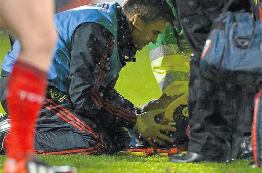 Niall Ronan receives medical attention on the pitch from Munster team physio Anthony Coole after suffering a neck injury against the Scarlets