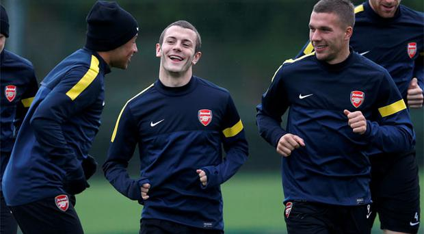 Arsenal's Alex Oxlade-Chamberlain (L) talks to Jack Wilshere (C) and Lukas Podolski during training. Photo: Reuters