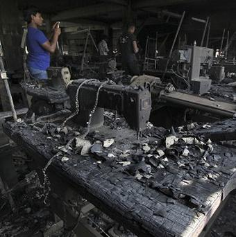 A man takes photographs inside a garment factory where a fire killed more than 110 people on the outskirts of Dhaka, Bangladesh (AP)