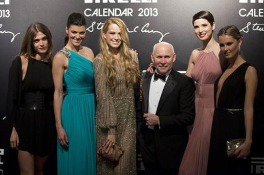 Photographer Steve McCurry poses with models at the 2013 Pirelli Calendar red carpet event.