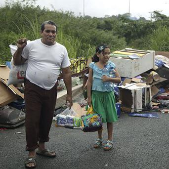 People whose home was affected by flooding hold donated food and water in Colon City, Panama (AP)