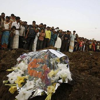 Hundreds of Bangladeshi mourners watch as victims of a fire in a garment factory are buried in Dhaka (AP)