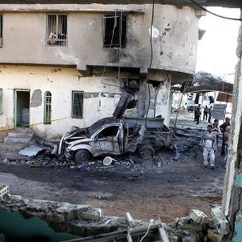 People inspect the scene of a bombing a busy commercial area in Hillah (AP)