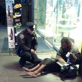 New York City police officer Larry DePrimo presents a barefoot homeless man in New York's Times Square with boots (Jennifer Foster/AP)