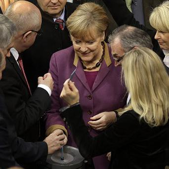 German Chancellor Angela Merkel casts her vote on the Greek loan rescue deal at the German federal parliament (AP)