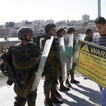 A Palestinian protester holds a placard in front of Israeli soldiers during a demonstration in the West Bank village of al-Masara near Bethlehem (AP)