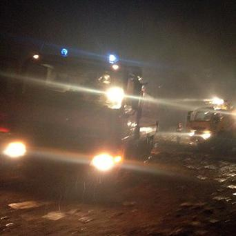 Emergency fire trucks at the crash site of a plane as rain falls, in Brazzaville, Republic of Congo (AP)