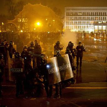 Riot police detain protesters outside the parliament building in Ljubljana, Slovenia (AP)
