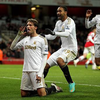 A Michu, left, brace gave Swansea a crucial victory over Arsenal at the Emirates Stadium