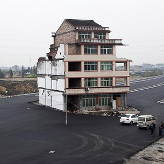 A house sitting in the middle of a new main road on the outskirts of Wenling city in east China's Zhejiang province has been demolished (AP Photo)
