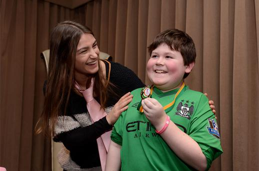 Jack McGuirk (9) from Swords, who is undergoing treatment in St Johns Ward in Crumlin Childrens Hospital receiving an Aoibheanns Pink Tie (APT) Gold Medal from Olympic Gold Medalist Boxer Katie Taylor