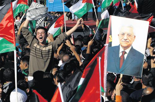 A Palestinian man cheers near a placard depicting President Mahmoud Abbas during a rally in the West Bank city of Ramallah, marking the UN's upgrading of Palestine to non-member state. Photo: Reuters