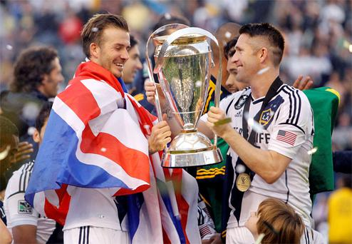 Robbie Keane hands David Beckham the trophy after the Galaxy defeated the Houston Dynamo to win the MLS Cup in 2012.