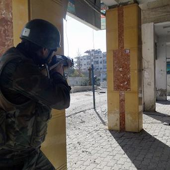 A Syrian soldier aims fire at rebels in Damscus (AP)