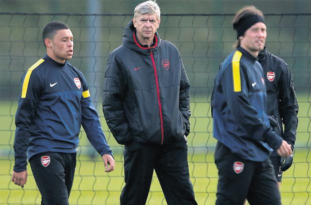 Arsenal manager Arsene Wenger keeps an eye on Alex Oxlade-Chamberlain and Tomas Rosicky during training yesterday ahead of tonight's game with Olympiakos