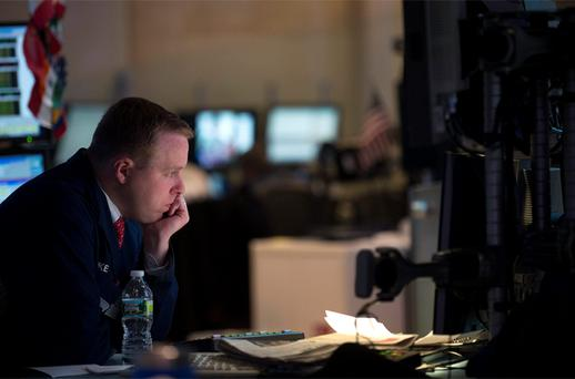 A trader looks over his monitor as he works on the floor of the New York Stock Exchange in New York. Photo: Reuters